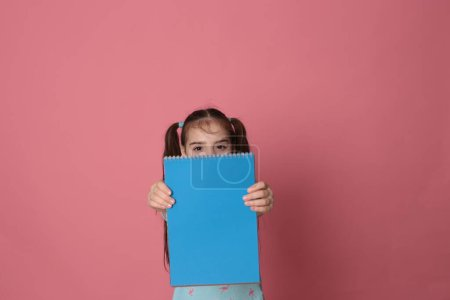 chica divertida de ocho años de edad sostiene una hoja de color de papel espacio libre para escribir sobre un fondo brillante