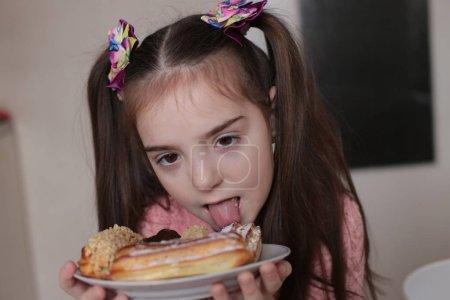 Photo pour Une fillette de huit ans mange un dessert délicieux et délicieux eclairs macro photo - image libre de droit