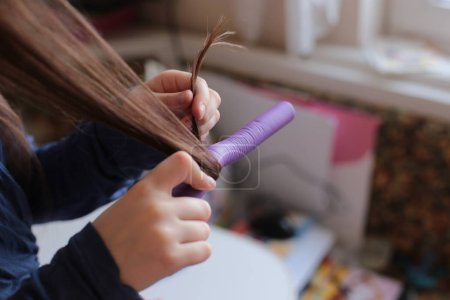 Photo pour Beautiful cheerful girl of eight years spins curlers on long hair - image libre de droit