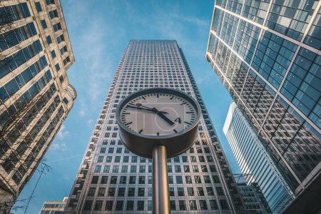 Photo pour Londres, Uk - mars 2016: Big horloges avec des gratte-ciel sur fond Canary Wharf. Notion de temps et d'affaires. - image libre de droit