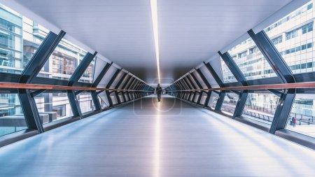 Photo pour Londres, Uk - mars 2016: Femme marchant dans un tunnel futuriste dans le quartier de Canary Wharf, quartier d'affaires important situé à Tower Hamlets, East London - image libre de droit