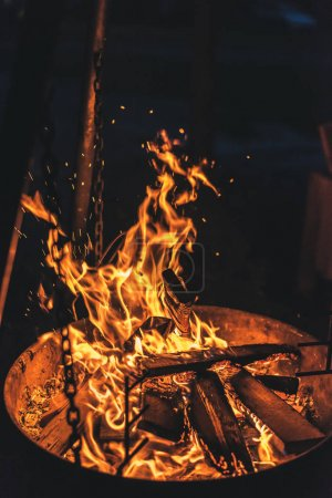 Camping bonfire at night with with marshmallow and burning woodpile