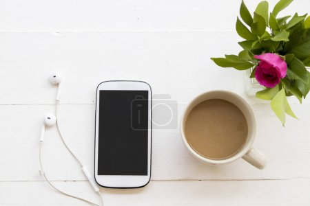 mobile phone earphone with hot coffee cup and flower on white table