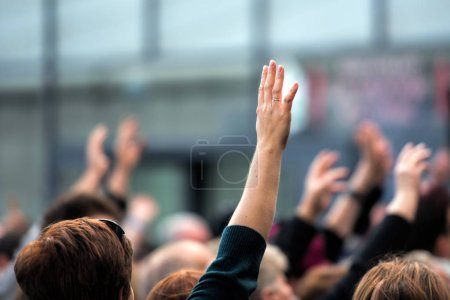 Crowd of people raises  hand, blurred background...