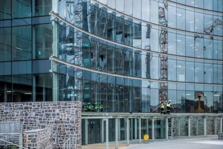 Photo pour Travailleurs nettoyage des fenêtres dans un bâtiment moderne - image libre de droit