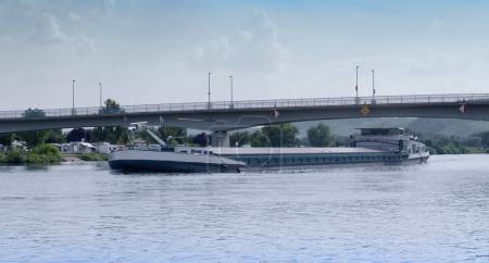 Photo pour Péniche sur l'eau de la rivière près du grand pont - image libre de droit