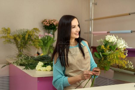 beautiful young girl with dark hair, in a flower shop collecting a bouquet