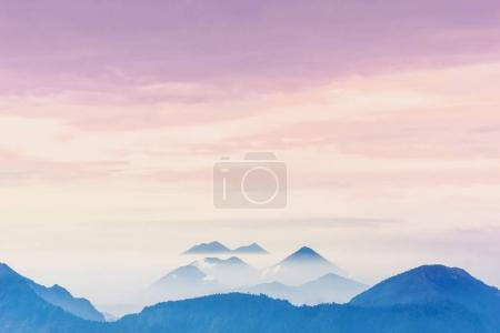Violet sunset over foggy volcanoes of Lago Atilan by Quetzaltenango in Guatemala