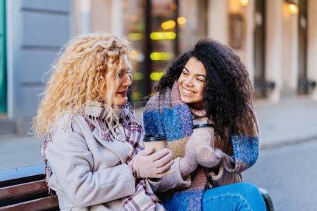 Foto de Cierre de dos razas mixtas multiétnicas maldita mujer que disfruta de un día soleado de invierno, sentado en el banco, bebiendo café juntos. Mujeres amigas se divierten después de visitar, viajar, concepto de inspiración.. - Imagen libre de derechos