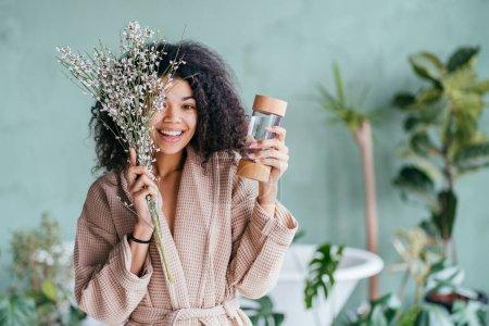 Photo pour Vivace femme multi-ethnique écologique couvrant les yeux avec une branche florissante et tenant une bouteille de boisson réutilisable, robe de chambre relaxante après le bain. Intérieur de la salle de bain écologique sur fond. - image libre de droit
