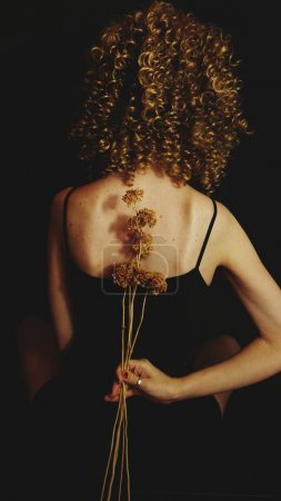 back of young curly woman with dry flowers on black background