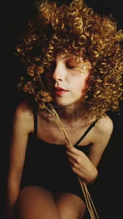 Portrait of young curly woman with dry flowers and closed eyes on black background