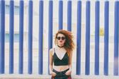Young redhead woman with sunglasses in black clothes posing with cool style outdoor on blue background