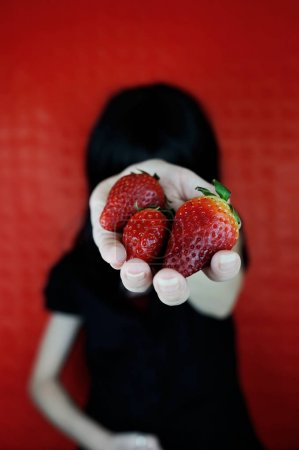 Portrait of young brunette woman with strawberries on red background