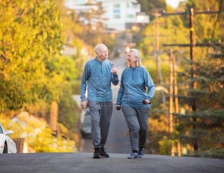 Senior couple walking along street on hill
