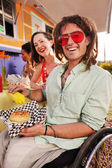 Smiling disabled man wearing red sunglasses pours mustard onto his burger