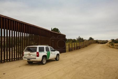 Border Patrol Driving Near Wall