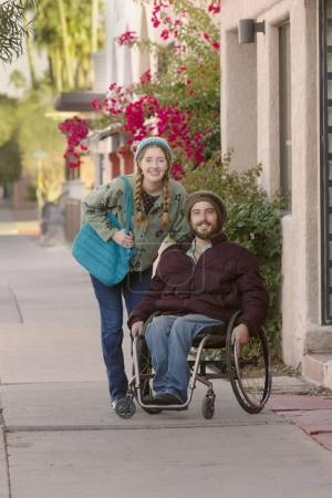 Young Woman and Man in Wheelchair on Sidewalk