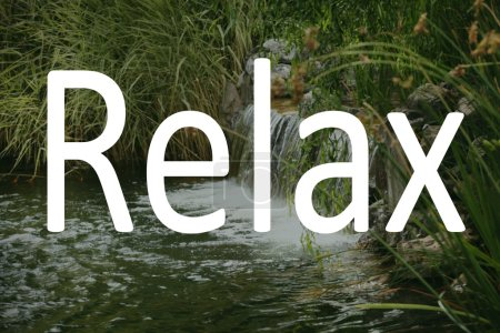 Word RELAX and small waterfall on background.