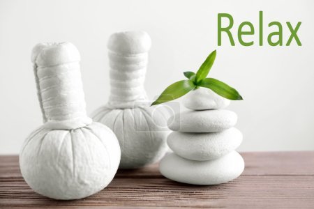 Spa composition with white stones and herbal massage stamps on wooden table. Word RELAX on light background.