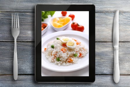 Photo for Table appointments and tablet. Photo of food on tablet screen. - Royalty Free Image