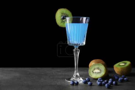 Delicious cocktail with kiwi slice and blueberries on gray table