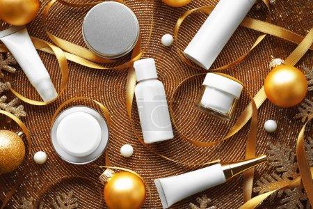 Photo pour Produits cosmétiques beauté avec décoration de Noël sur fond mat perlé or - image libre de droit