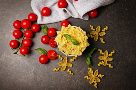 Photo for Plate with farfalle pasta and tomatoes on table - Royalty Free Image