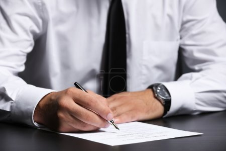 Man signing last will and testament, closeup