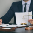 Scales of justice and businessman sitting at table...