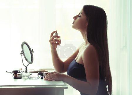 Photo pour Belle jeune femme regardant dans le miroir pendant l'utilisation de parfum - image libre de droit