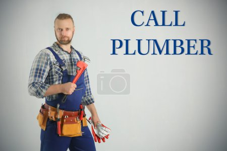 Call Plumber. Handsome plumber with pipe wrench and gloves on light background
