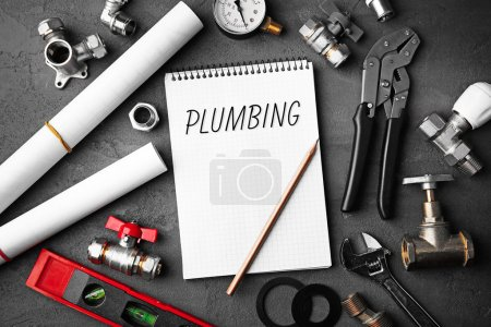 Plumbing concept. Notebook and plumber tools with blueprints on concrete structure background
