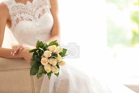 Mariée en belle robe avec bouquet de mariée assise sur canapé