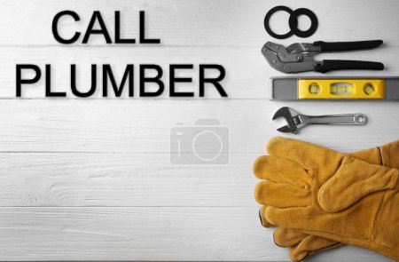 Call Plumber. Plumber tools on white wooden background