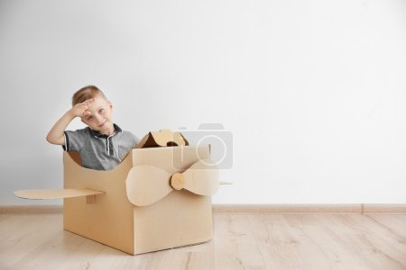 Photo for Little boy playing with cardboard airplane on white wall background - Royalty Free Image
