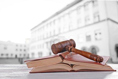 Photo pour Le marteau du juge et les livres sur le fond flou du bâtiment - image libre de droit