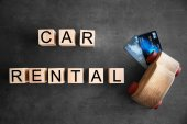 Cubes with words CAR RENTAL and wooden toy on grey background, top view