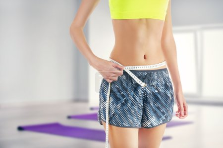 Sporty woman with measuring tape on waist against blurred gym background. Sport and diet concept.