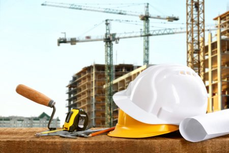 Construction blueprints with tools and helmets on building construction background