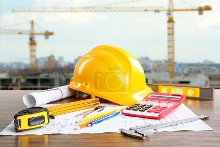 Photo pour Plans de construction avec outils et casque sur fond de construction de bâtiment - image libre de droit