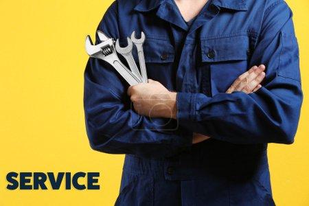 Photo pour Mécanicien avec bras croisés et clé debout sur fond jaune - image libre de droit