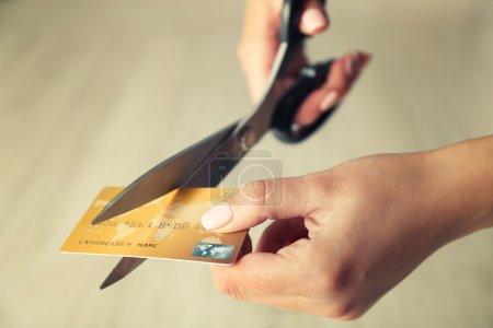 Photo pour Mains féminines coupe de carte de crédit avec des ciseaux - image libre de droit