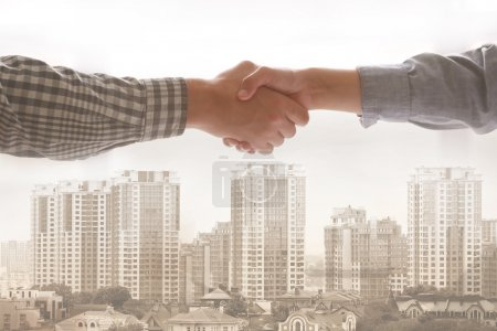 Logistics concept. Double exposure. Business people handshaking and cityscape background