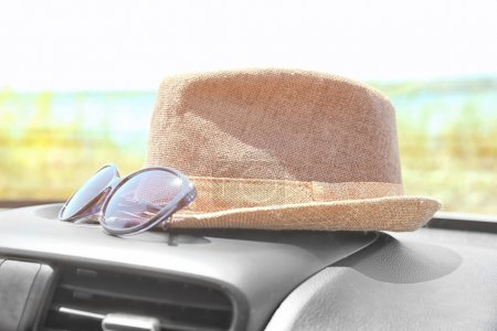 Hat with sunglasses on dashboard