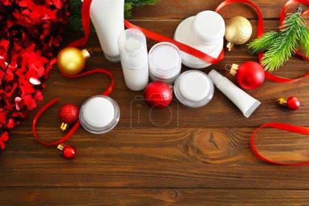Photo pour Produits cosmétiques beauté avec décoration de Noël sur fond en bois - image libre de droit