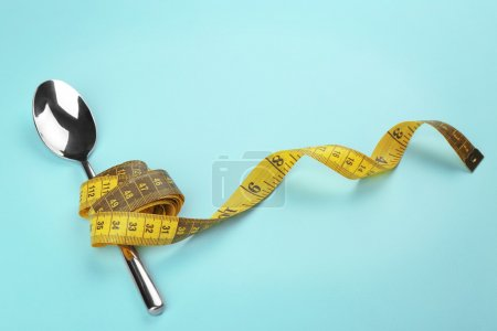 Yellow measuring tape wrapped around spoon lying on color surface. Diet concept