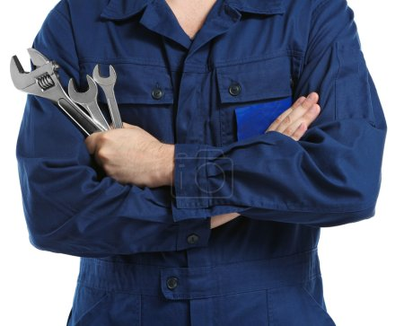 Mechanic in uniform with crossed arms and wrenches standing on white background