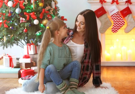 Beautiful young woman with daughter in living room decorated for Christmas