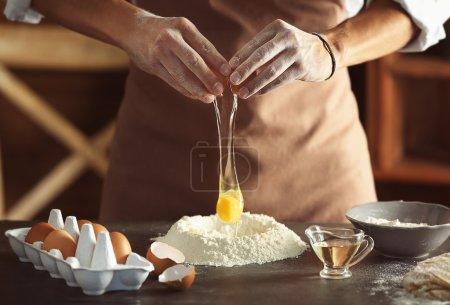 Man preparing dough on kitchen table, close up view